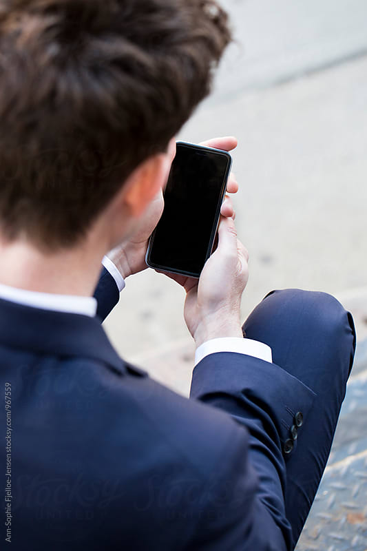 Man in a suit on his phone by Ann-Sophie Fjelloe-Jensen for Stocksy United