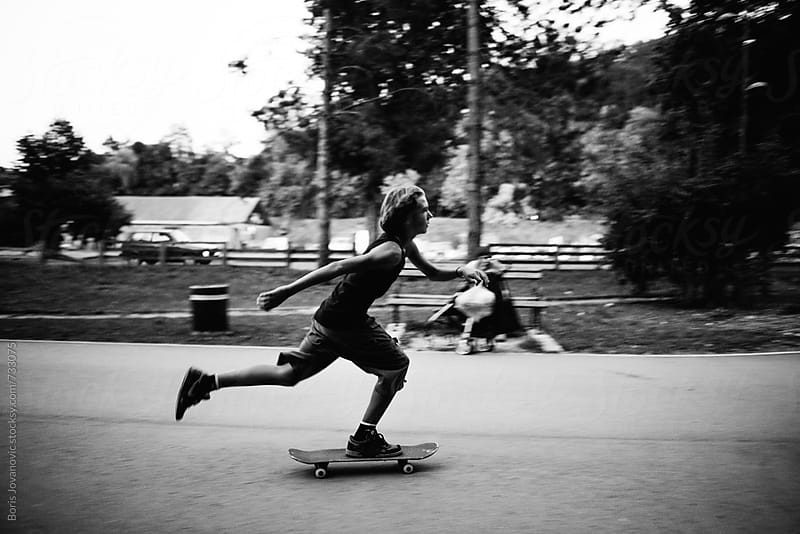 Boy riding a skateboard by Boris Jovanovic for Stocksy United