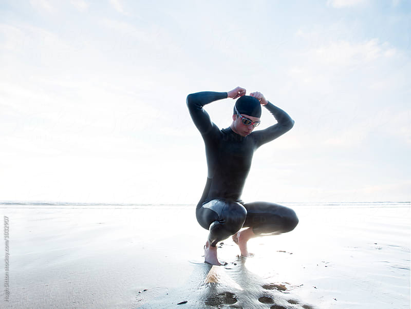 Triathlete on beach after swim.  by Hugh Sitton for Stocksy United