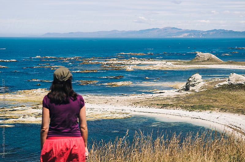 Woman looking out over the ocean, Kaikoura, New Zealand. by Thomas Pickard for Stocksy United