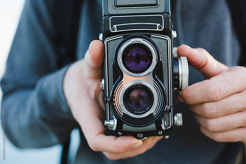 Man holding an old camera. by michela ravasio for Stocksy United