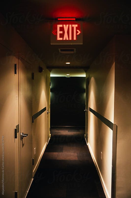 Hotel empty passage way with an exit sign above by Alejandro Moreno de Carlos for Stocksy United