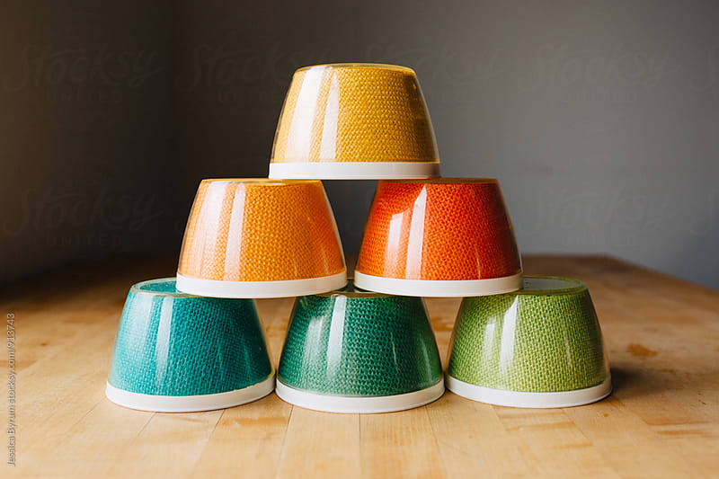 Colorful vintage burlap bowls stacked on kitchen table. by Jessica Byrum for Stocksy United