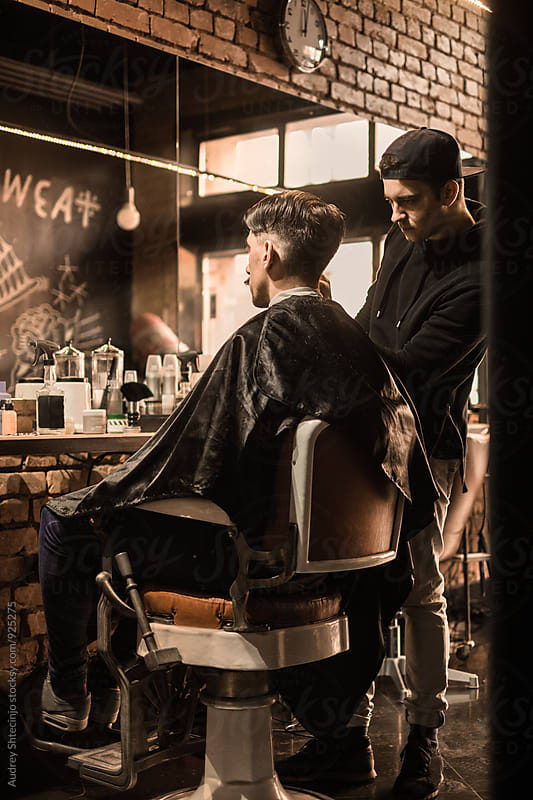 Young barber giving client a classic haircut in vintage barber shop by Audrey Shtecinjo for Stocksy United