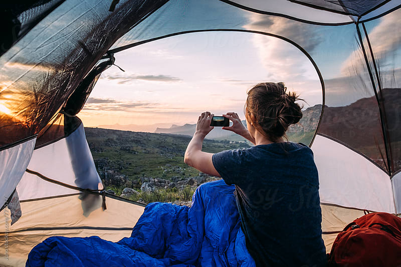 Woman sitting in her tent taking a photo of the sunset with her mobile phone by Micky Wiswedel for Stocksy United