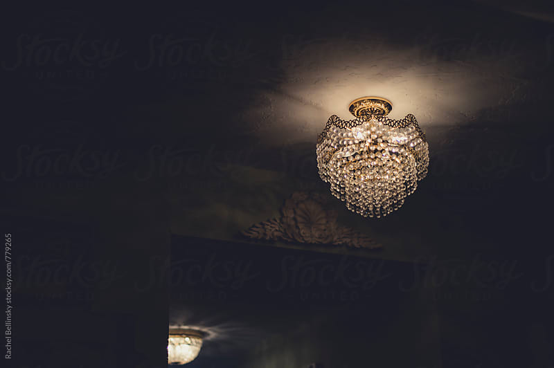 An old crystal chandelier in a dimply lit room by Rachel Bellinsky for Stocksy United