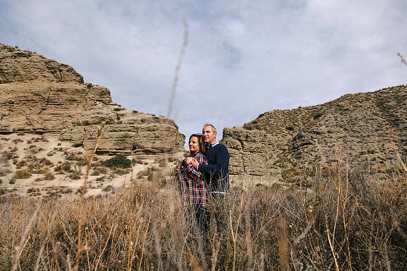 Mid Adult Couple in a Desertic Landscape by Victor Torres for Stocksy United
