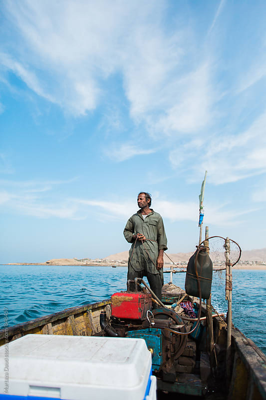 A fisherman and captain standing high on his boat by Murtaza Daud for Stocksy United