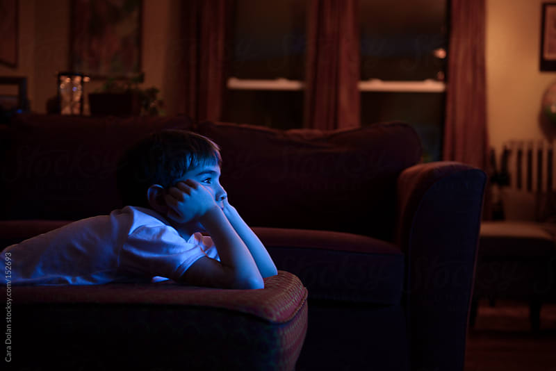 Boy watches television at home by Cara Dolan for Stocksy United