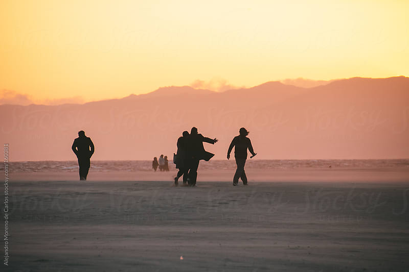 Silhouettes of people walking on the sand of a beach at sunset by Alejandro Moreno de Carlos for Stocksy United