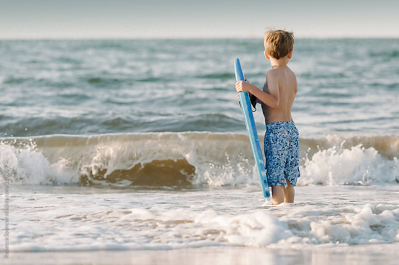 Boy facing waves holding surf board by Rebecca Spencer for Stocksy United