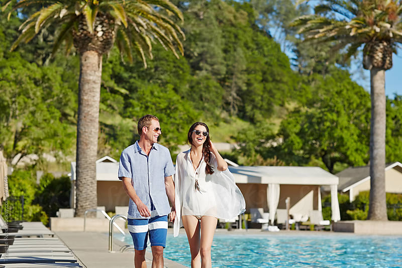 Beautiful couple relaxing by pool at luxury resort by Trinette Reed for Stocksy United