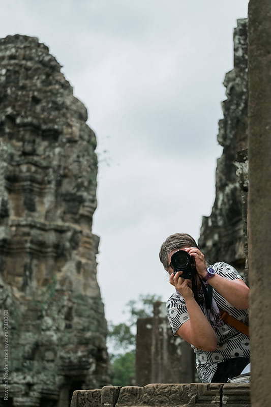 Tourist photogrpaher at Bayon Temple, Siem Reap, Cambodia by Rowena Naylor for Stocksy United