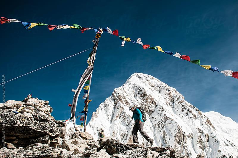 Female trekker beneath prayer flags, Kala Pattar (5,545 metres), Everest Region, Sagarmatha National Park, Nepal. by Thomas Pickard for Stocksy United