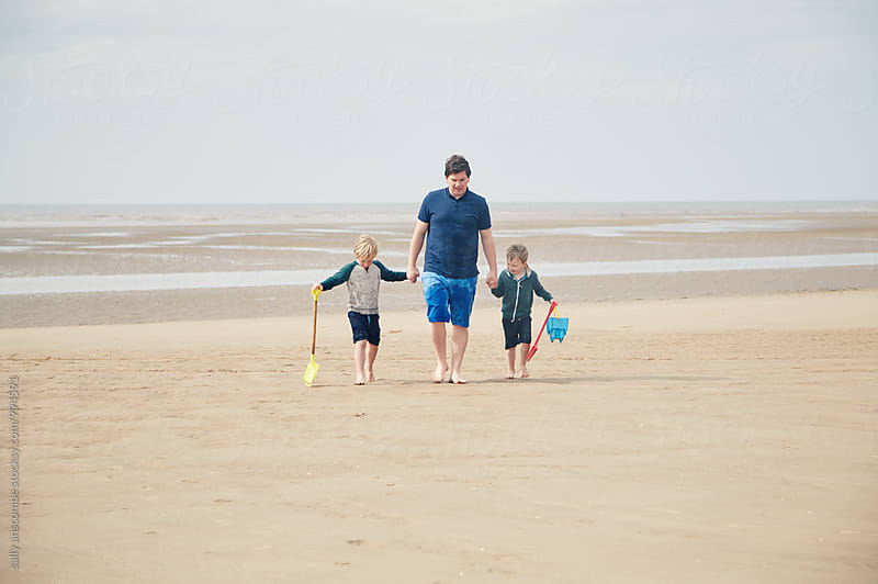 Father and sons on the beach together by sally anscombe for Stocksy United