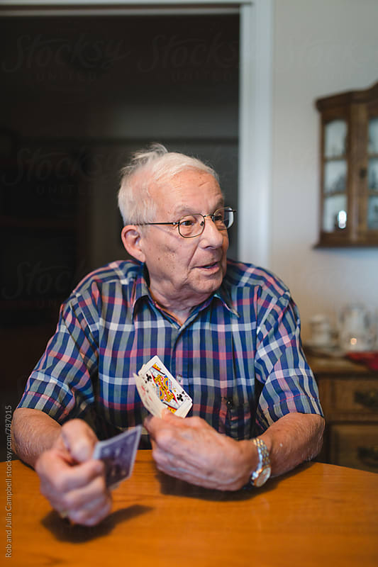 Senior man playing card game at table inside by Rob and Julia Campbell for Stocksy United