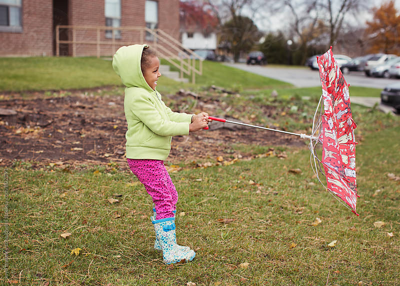 Portrait of young girl fighting with her umbrella on a windy fall day by anya brewley schultheiss for Stocksy United