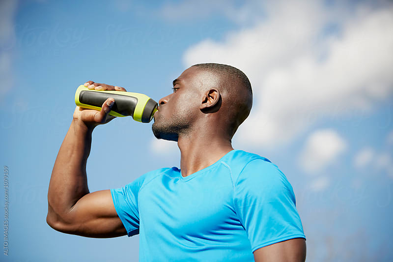 Male Runner Drinking Water Against Sky by ALTO IMAGES for Stocksy United