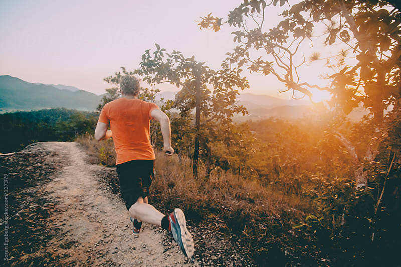 Man running trail outside in nature with trees at sunset. by Soren Egeberg for Stocksy United