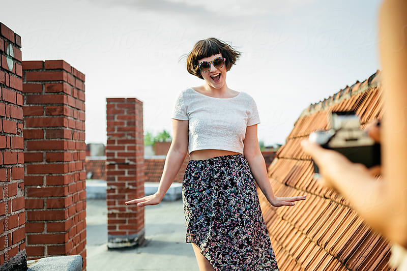 Young woman being photographed on a rooftop by VegterFoto for Stocksy United