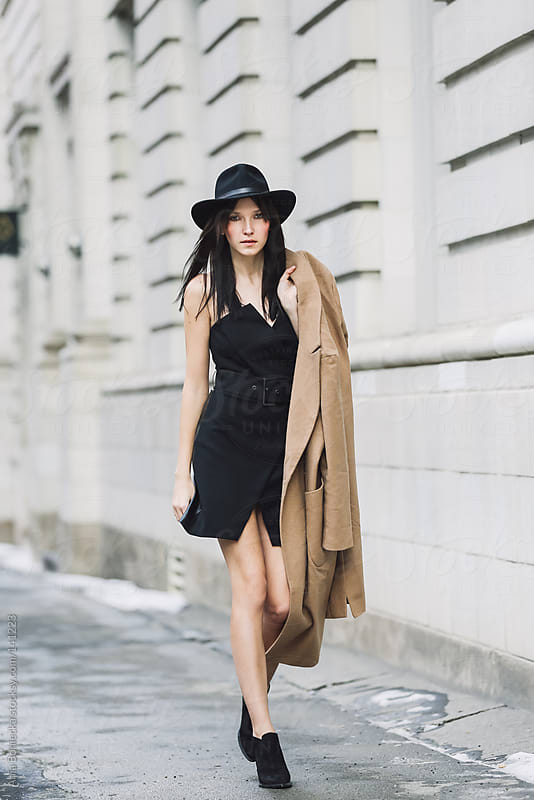 A beautiful woman walking with her jacket slung over her shoulder by Ania Boniecka for Stocksy United