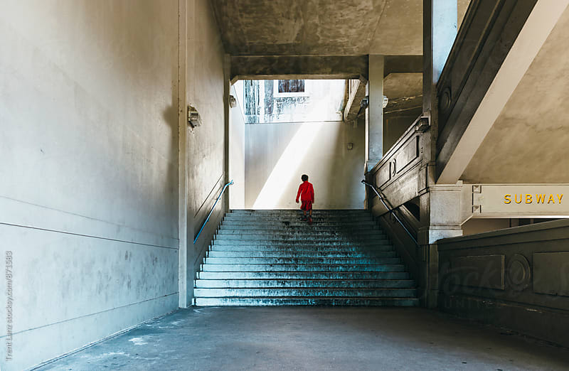 Boy climbing up steps in subway by bribge by Trent Lanz for Stocksy United
