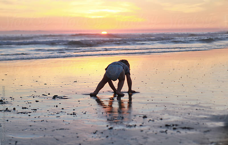 Toddler at beach playing in sand during sunset by Dina Giangregorio for Stocksy United