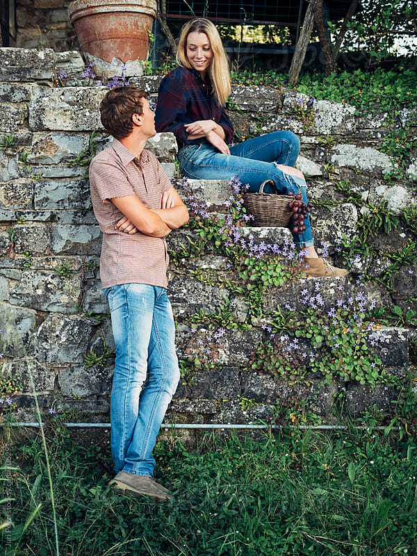 couple sitting on an old stone wall by Juri Pozzi for Stocksy United