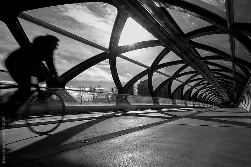 Cyclist rides over modern pedestrian bridge by Riley J.B. for Stocksy United
