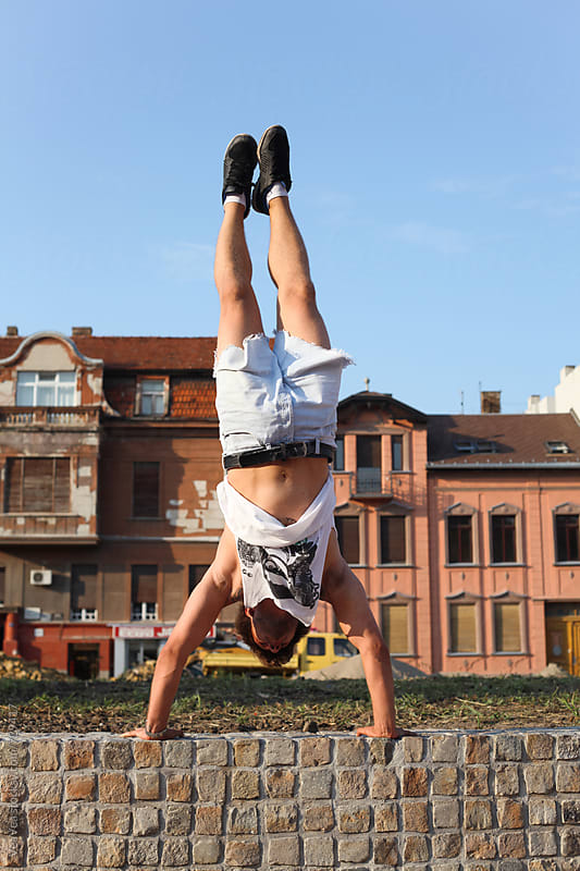 Man doing cartwheel in the city by Marija Mandic for Stocksy United