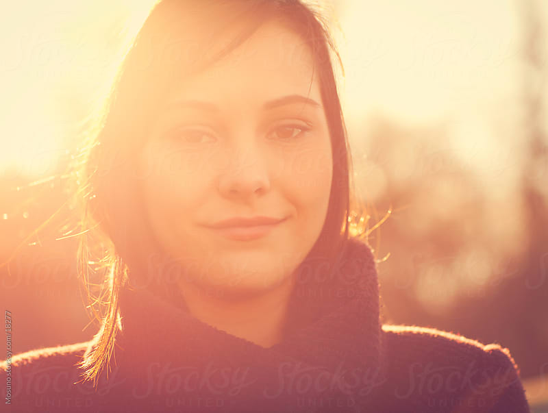 Portrait of a young woman backlit by the setting sun. by Mosuno for Stocksy United