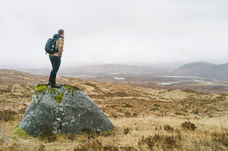 A male hiker or walker standing on a rock overlooking the Scottish highlands by Ivo de Bruijn for Stocksy United