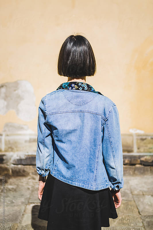 Nerdy Young Woman with Denim Blue Jacket from Behind by Giorgio Magini for Stocksy United