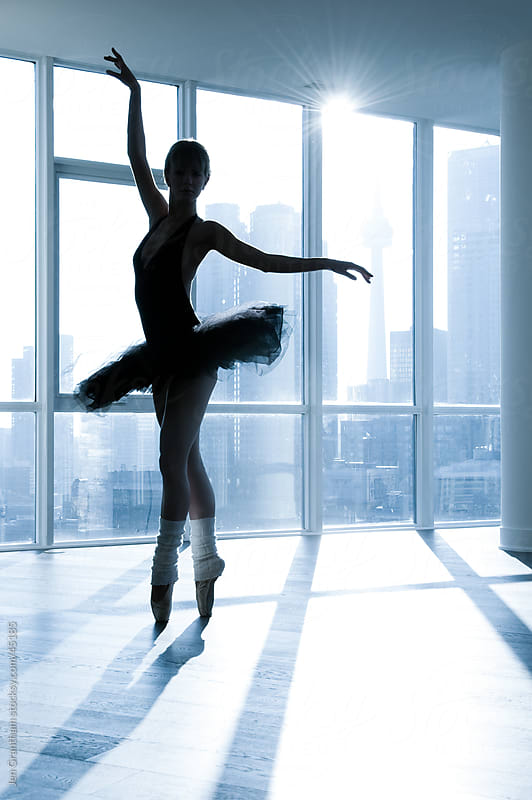 Ballerina in silhouette in front of a window by Jen Grantham for Stocksy United