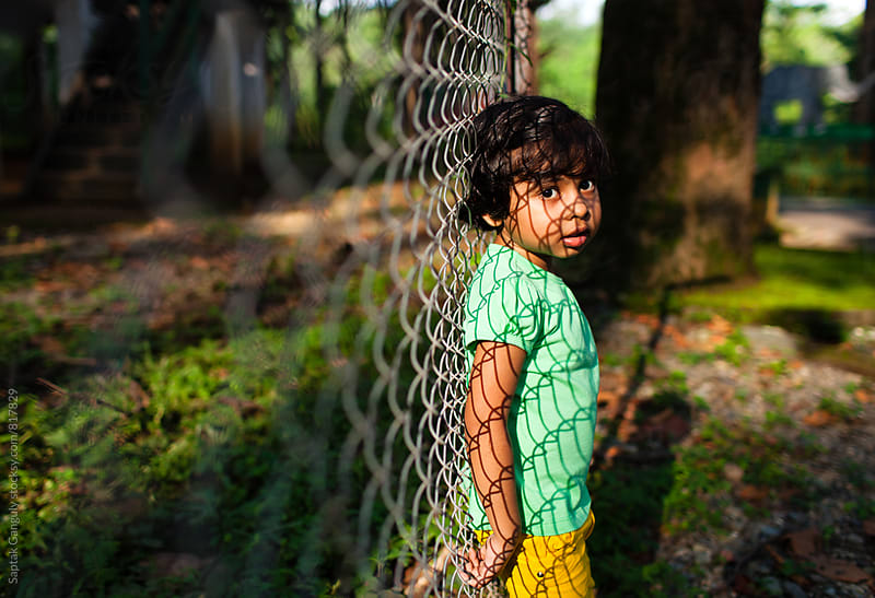 Little girl in serious mood standing by the fence by Saptak Ganguly for Stocksy United