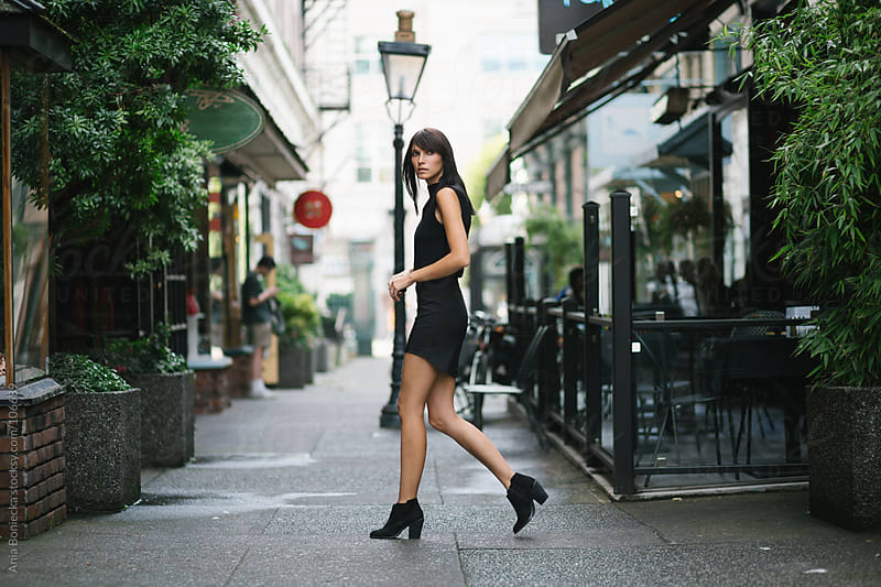 A woman walking in an alley  by Ania Boniecka for Stocksy United