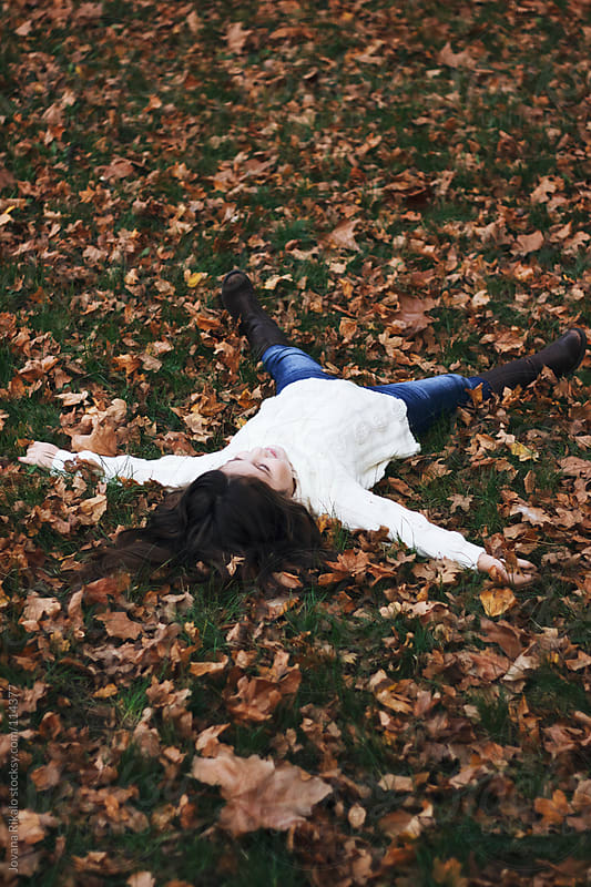 Little girl lie down in autumn leaves in the park by Jovana Rikalo for Stocksy United