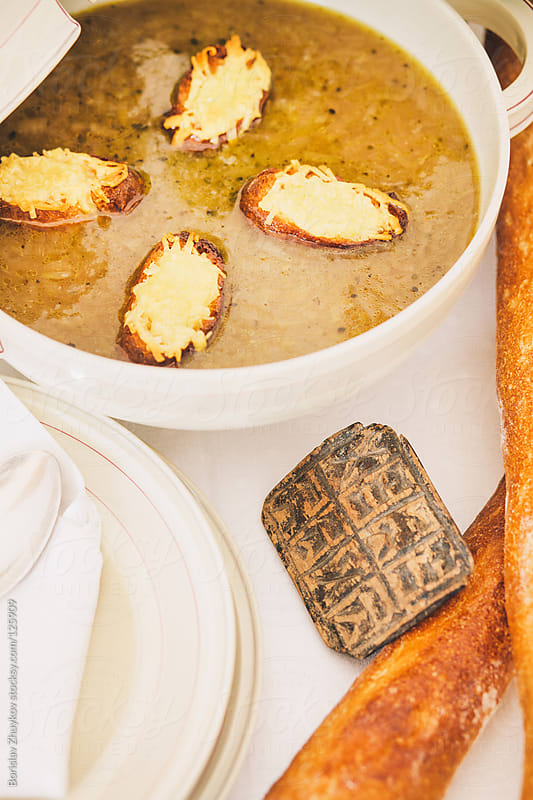 Onion soup and baguettes with cheese by Borislav Zhuykov for Stocksy United