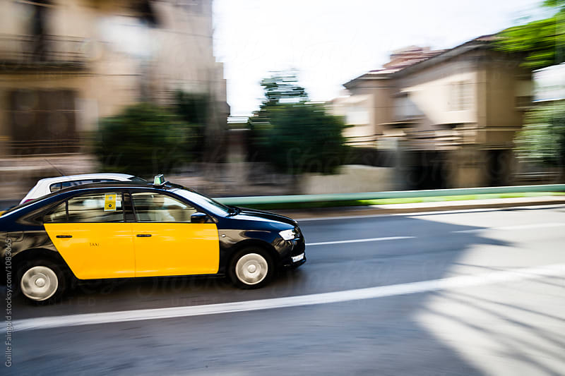 Barcelona's taxi driving along road by Guille Faingold for Stocksy United