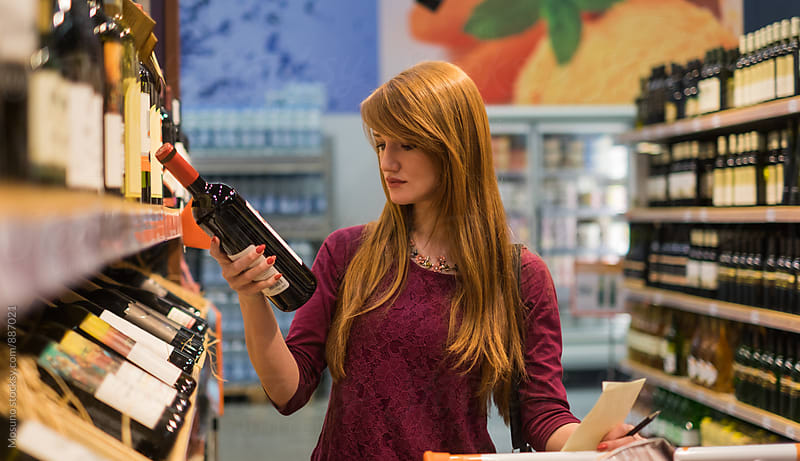Ginger Woman Buying Wine in a Supermarket by Mosuno for Stocksy United
