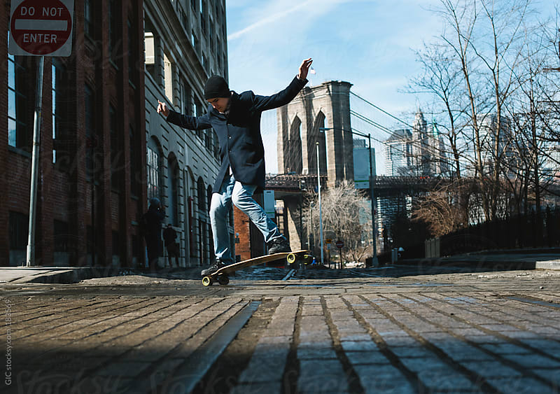 Young man with a skate in Dumbo, Brooklyn by GIC for Stocksy United