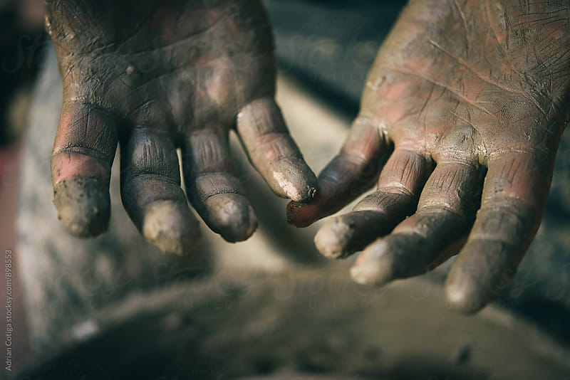 Close up of potter's dirty hands. by Adrian Cotiga for Stocksy United