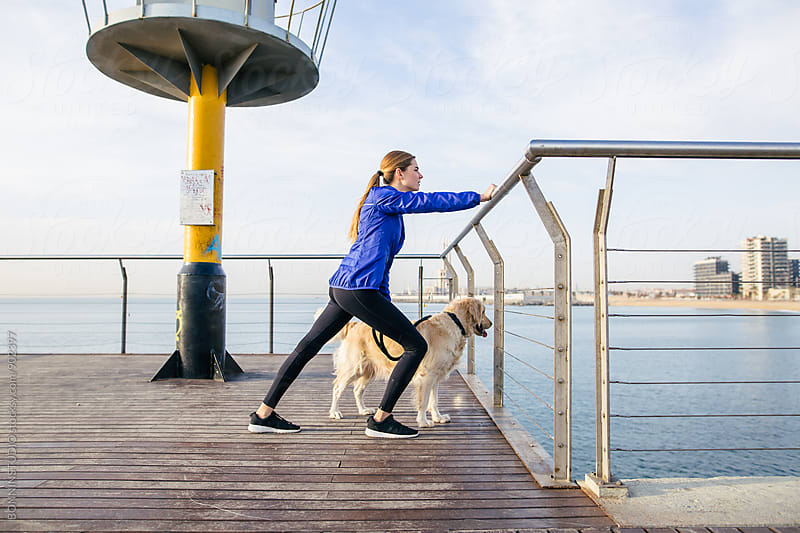 Runner woman doing stretching exercises with her dog on the bridge. by BONNINSTUDIO for Stocksy United
