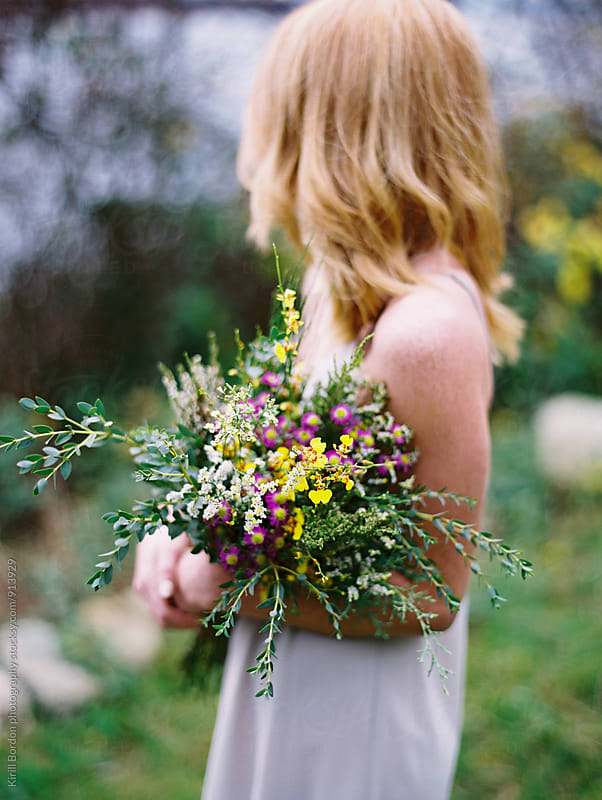 young woman holding wild flowers by Kirill Bordon photography for Stocksy United