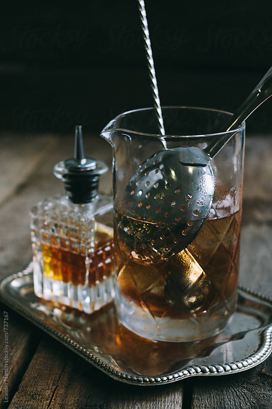 classic manhattan cocktail ingredients in a mixing tumbler on a salver by Leander Nardin for Stocksy United