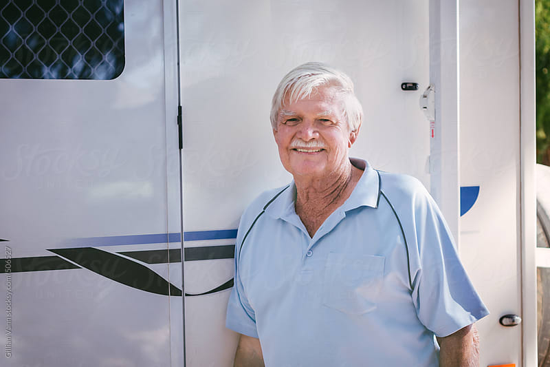 portrait of a retired man in front of his caravan by Gillian Vann for Stocksy United