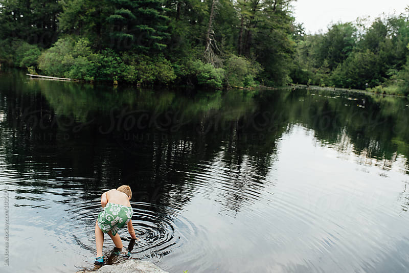 boy playing in the lake by Léa Jones for Stocksy United