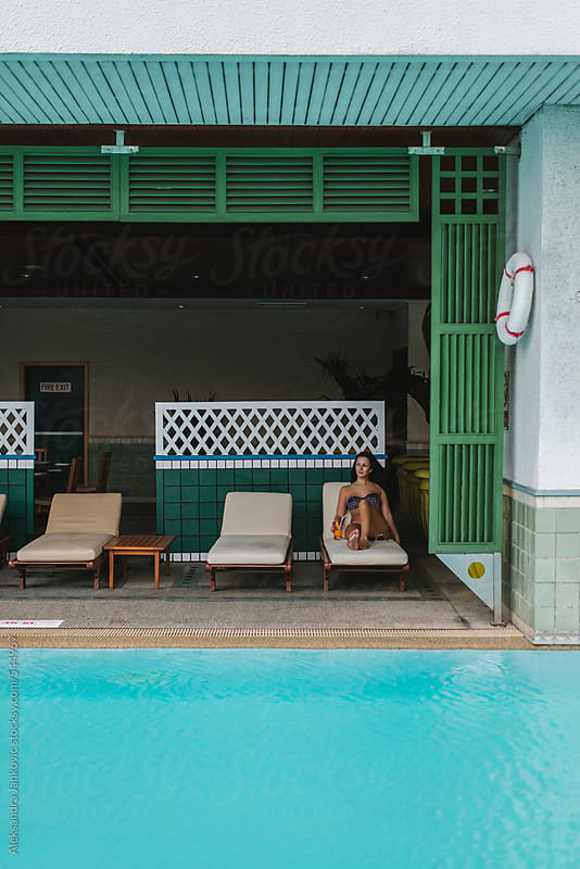 Woman relaxing by the pool by Aleksandra Jankovic for Stocksy United