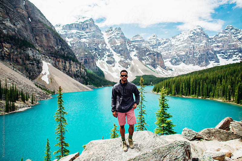A man standing in front of a blue lake with a mountain landscape by Kristen Curette Hines for Stocksy United