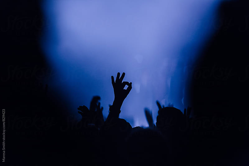 A silhouette 'ok' hand gesture in a dark crowd at an indoor gig by Maresa Smith for Stocksy United